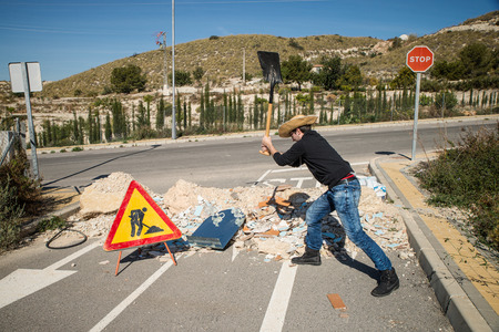 inefficient: Young guy building a road block with construction rubble, a concept