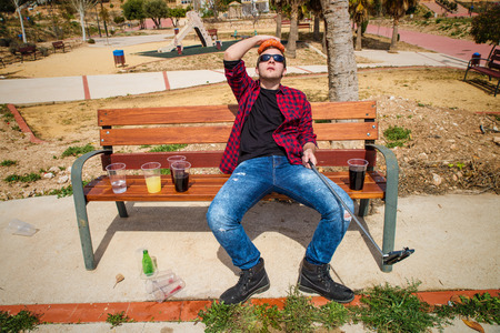 hangover: Guy documenting his hangover on a park bench with a selfie, a concept