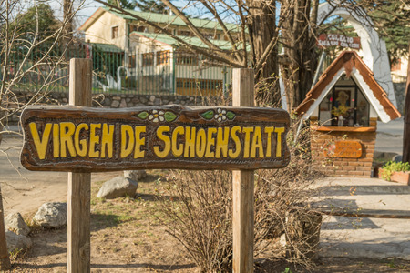 reminding: VILLA GENERAL BELGRANO, ARGENTINA - AUGUST 25 2015: Sign and small chapel reminding the German origin of its settlers Editorial