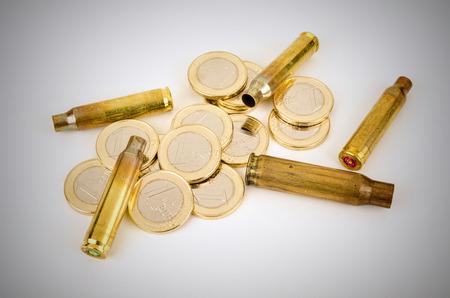 white collar crime: Bullet shells and coins,  a financial crime concept Stock Photo