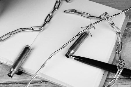 withhold: Bullets and barbed wire against  pen and notebook,  a press freedom concept