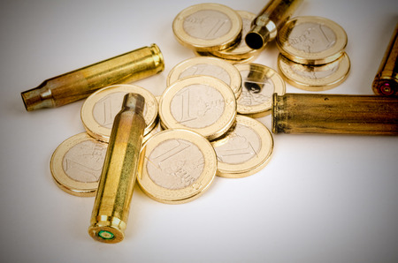 felony: Bullet shells and coins,  a financial crime concept Stock Photo