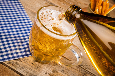 pilsner glass: Pooring cold lager from a large bottle Stock Photo