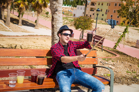 booze: Guy taking a selfie while surrounded by booze on a park bench