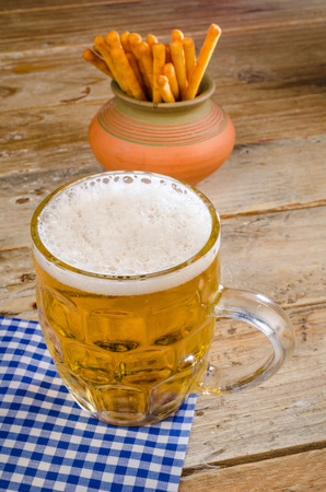 gressins: Stein of beer and breadsticks on a rustic  wooden table