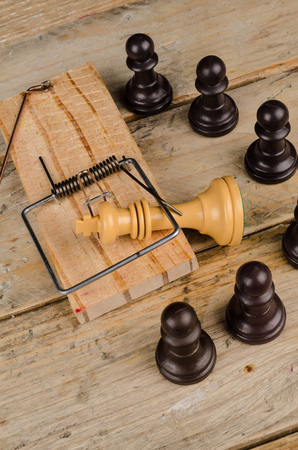 upheaval: King  in a mousetrap surrounded by pawns, a concept Stock Photo