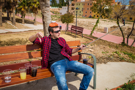 documenting: Guy documenting his hangover on a park bench with a selfie, a concept