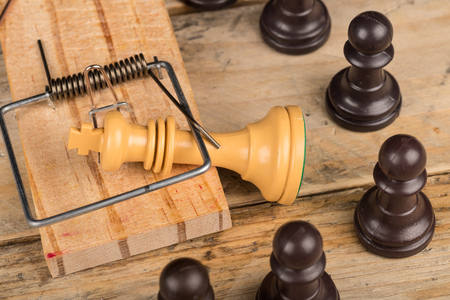 King  in a mousetrap surrounded by pawns, a concept Stock Photo