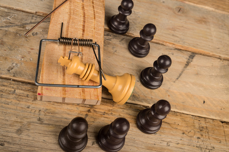 mousetrap: King  in a mousetrap surrounded by pawns, a concept Stock Photo