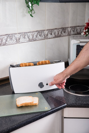 domestic kitchen: Toasting bread in a domestic kitchen Stock Photo