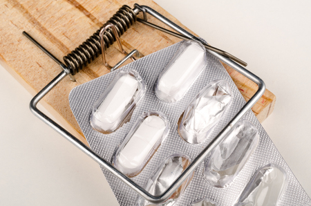 pharma: Pills caught by a mouse trap, a pharma addiction concept Stock Photo