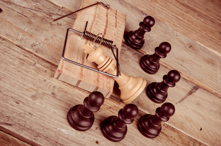 surrounded: King  in a mousetrap surrounded by pawns, a concept Stock Photo