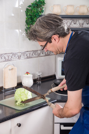 clipper: Clueless guy chopping lettuce with a hedge clipper Stock Photo
