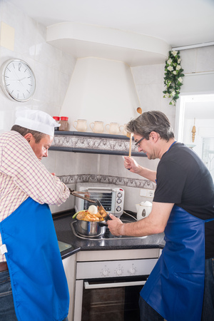 forties: Two males in their forties doing everything wrong while trying to cook. Stock Photo