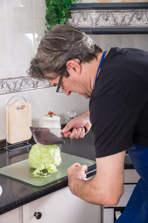 spoilt: Guy trying to chop lettuce with a meat cleaver