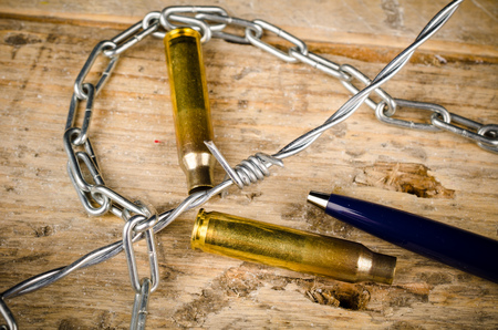 dictatorship: Bullets and barbed wire around a pen, a press freedom concept Stock Photo