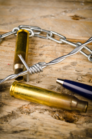 withhold: Bullets and barbed wire around a pen, a press freedom concept Stock Photo