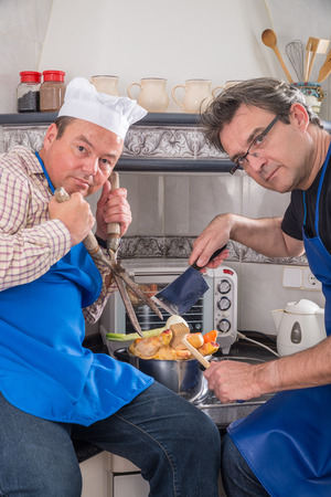 too many: Too many cooks spoil the broth, a conceptual shot with two useless male cooks.