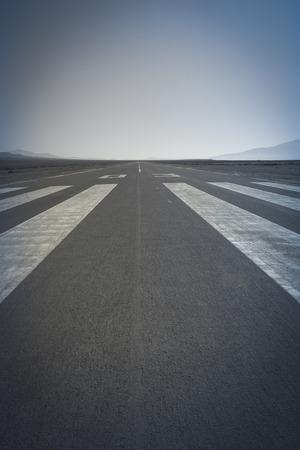 threshold: Long paved runway shot from its threshold markings