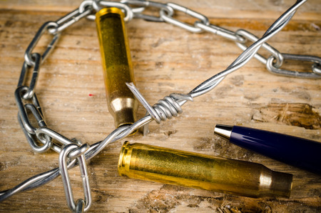 repression: Bullets and barbed wire around a pen, a press freedom concept Stock Photo