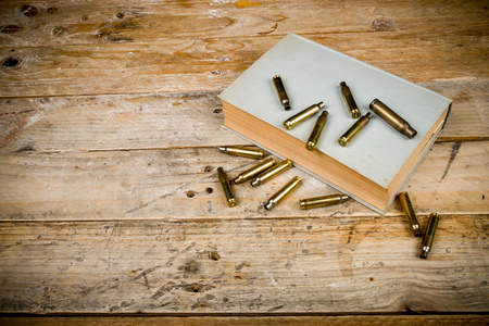 Still life  with old book and bullets, a mystery novel concept