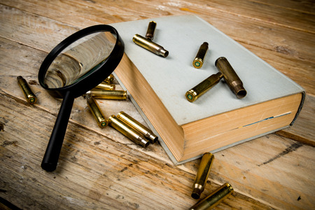organized crime: Detective novel concept  with book, bullets and magnyfying glass
