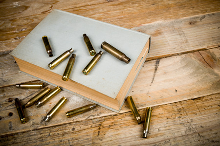 organized crime: Still life  with old book and bullets, a mystery novel concept
