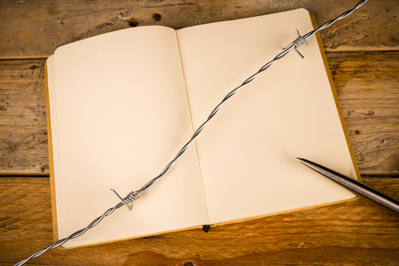 censorship: Notebook and pen  with barbed wire, a press censorship concept