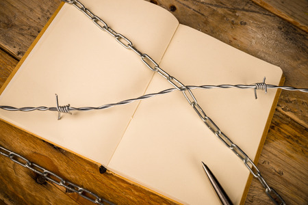 repression: Notebook and pen  with barbed wire, a press censorship concept