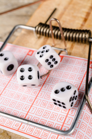 Dice and lottery ticket in a mousetrap, a concept Stock Photo
