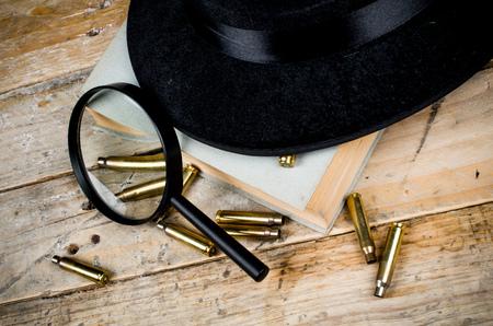film noir: Fedora hat, bullets and magnifying glass, a film noir concept