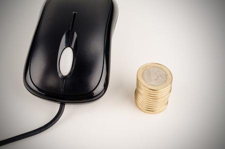 compras compulsivas: ratón del ordenador y una pila de monedas, el concepto de un e-commerce