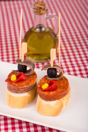 andalusian cuisine: Spanish chorizo tapa with anchovies served on a checkered tablecloth