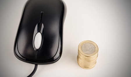 compulsive: Computer mouse and a stack of coins, an e-commerce concept