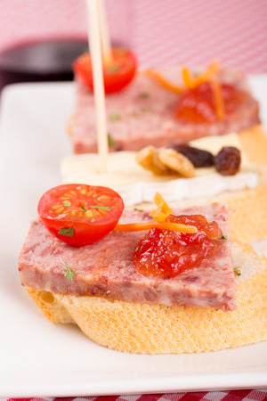 toothpick: Serving of traditional Spanish pate tapa on a checkered tablecloth Stock Photo