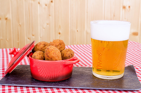 andalusian cuisine: Portion of freshly fried cod fish croquettes served with beer, a Spanish tapa  Stock Photo
