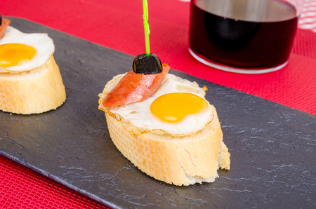 andalusian cuisine: Pincho style tapa with a fried quail egg with garnish Stock Photo