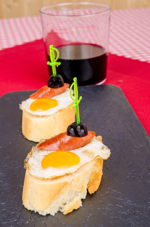 toothpick: Pincho style tapa with a fried quail egg with garnish Stock Photo