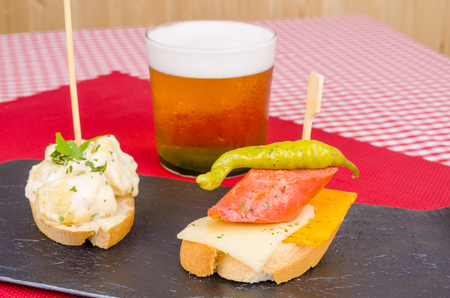 Pincho tapas, a slice of bread with an appetizer skewered on top, a Spanish cuisine  classic