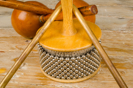 triangle musical instrument: Assorted traditional small percussion instruments on a wooden background