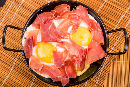 andalusian cuisine: Small tapa sized casserole with a serving of serrano ham with eggs Stock Photo