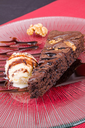 walnut cake: Wedge of chocolate walnut cake served with ice cream and garnished with chocolate syrup Stock Photo