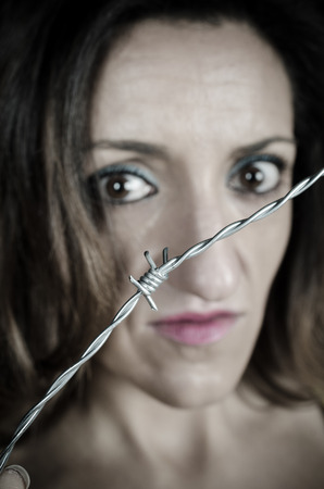 Scared woman behind barbed wire, a conceptual shot on gender violence
