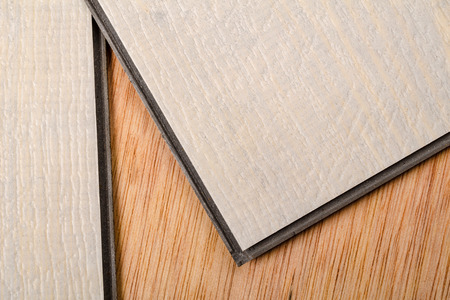 floor covering: Detail take of two vinyl flooring tiles ready to be matched by their lips and grooves