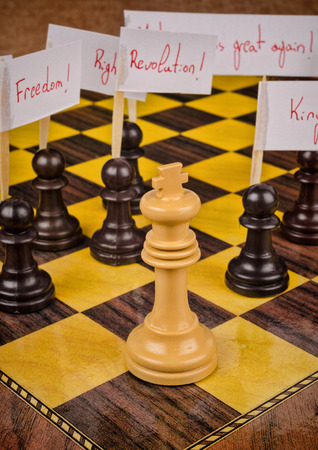 protester: Pawns demonstrating against the king, a social unrest concept on a chess board Stock Photo