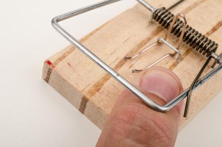Finger caught by a mousetrap, a conceptual shot