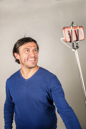 narcissist: Hispanic guy making faces  using a selfie stick