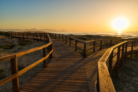 Wooden walkway down to a sandy beach with dunes on Costa Blanca, Alicante, Spain