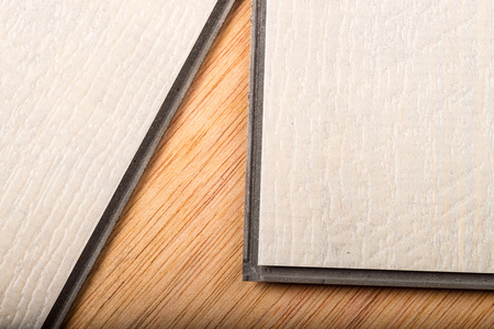 Detail take of two vinyl flooring tiles ready to be matched by their lips and grooves
