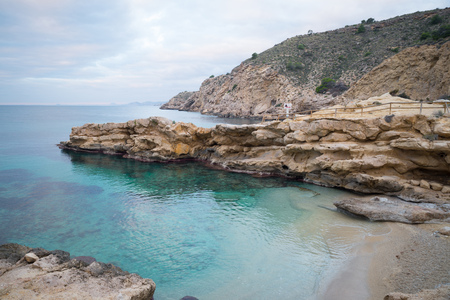 Conill, one of the most popular nudist beaches on Costa Blanca, Spain, amidst scenic rocky landscape Stock Photo
